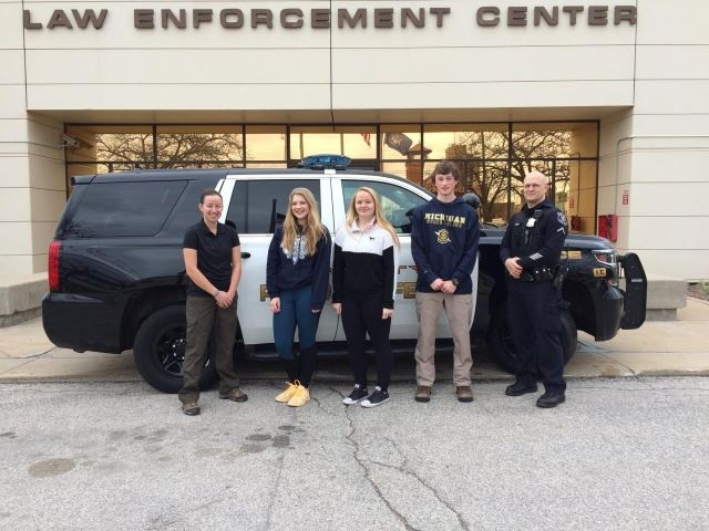Explorers in front of Police cruiser